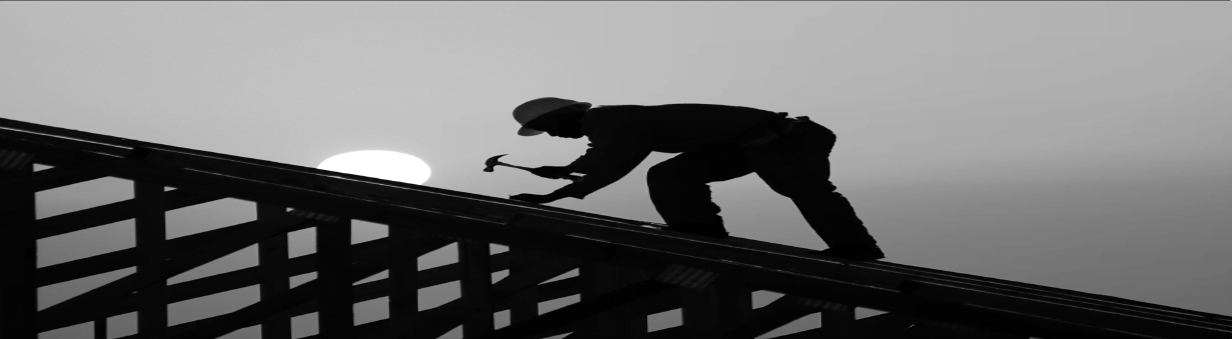 a labor worker working on a roof with hammer